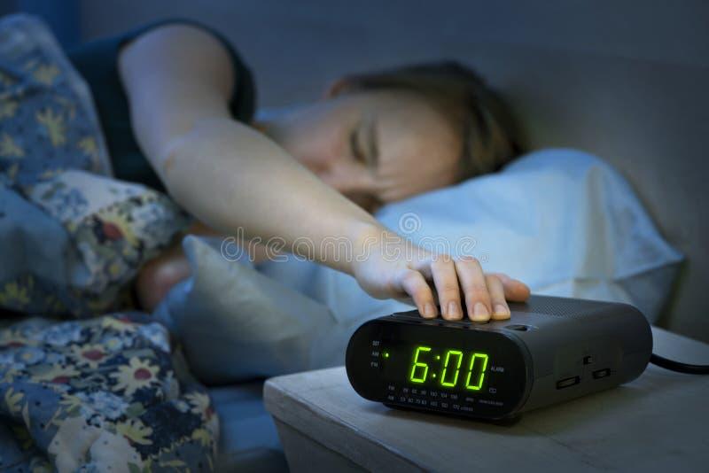 早早醒与闹钟的妇女 免版税库存图片