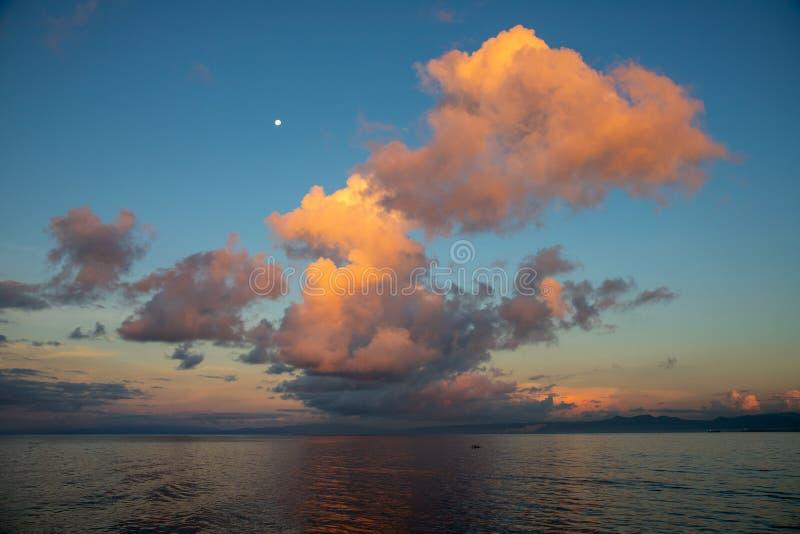 早晨与橙色云彩和月亮的露水天空 海边与月亮和云彩的日出照片 橙色日落或日出 免版税库存图片