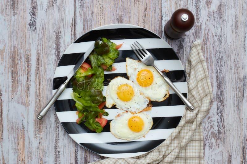 早晨健康早餐荷包蛋用沙拉用新鲜的莴苣和菜 在一张老,轻,破旧的桌上的一块板材与 免版税库存图片