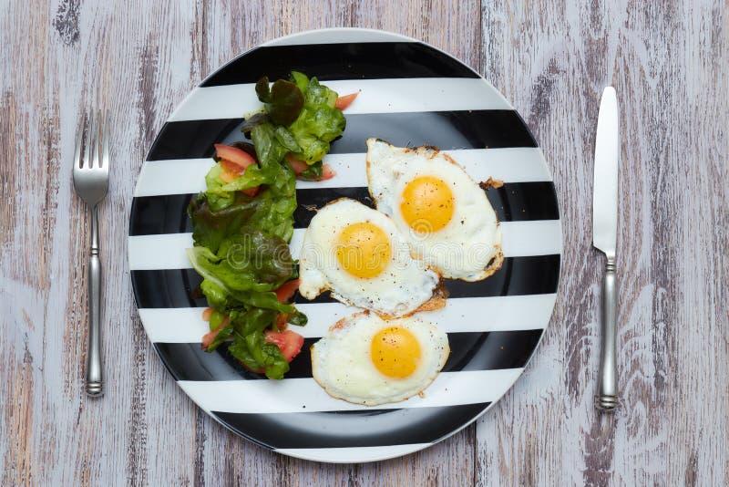 早晨健康早餐荷包蛋用沙拉用新鲜的莴苣和菜 在一张老,轻,破旧的桌上的一块板材与 库存图片