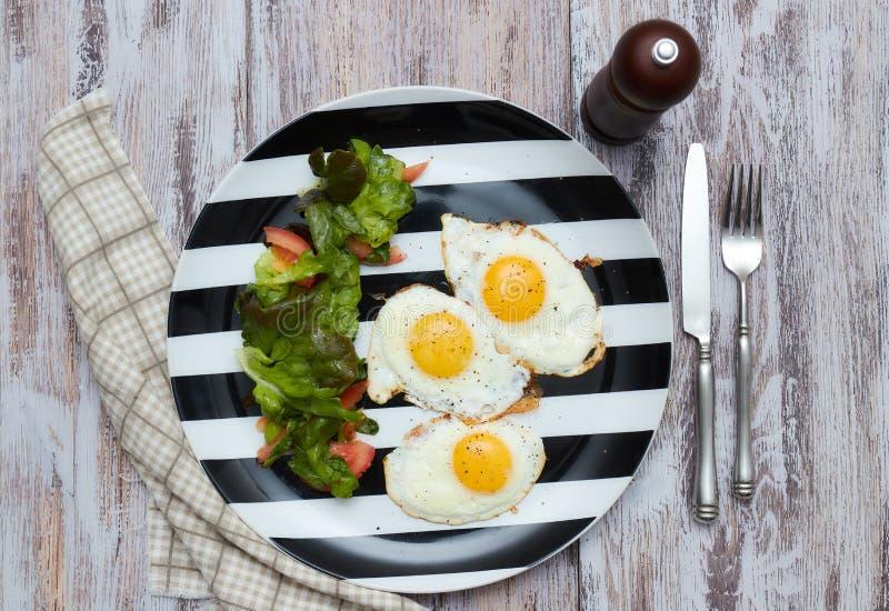 早晨健康早餐荷包蛋用沙拉用新鲜的莴苣和菜 在一张老,轻,破旧的桌上的一块板材与 免版税库存照片
