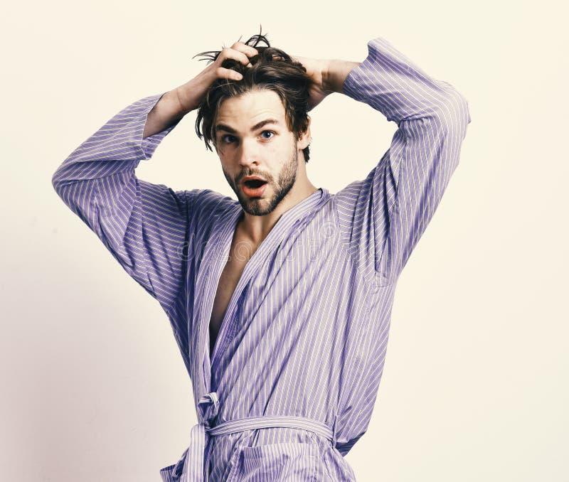 早晨和淋浴概念 有胡子的人在灰色背景的蓝色晨衣 蓝色浴巾的有胡子的强壮男子 免版税库存图片