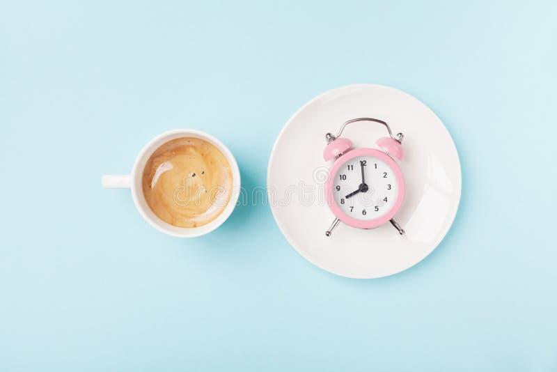 早晨咖啡和闹钟在蓝色运作的桌面看法 早餐时间概念 平的位置样式 库存照片