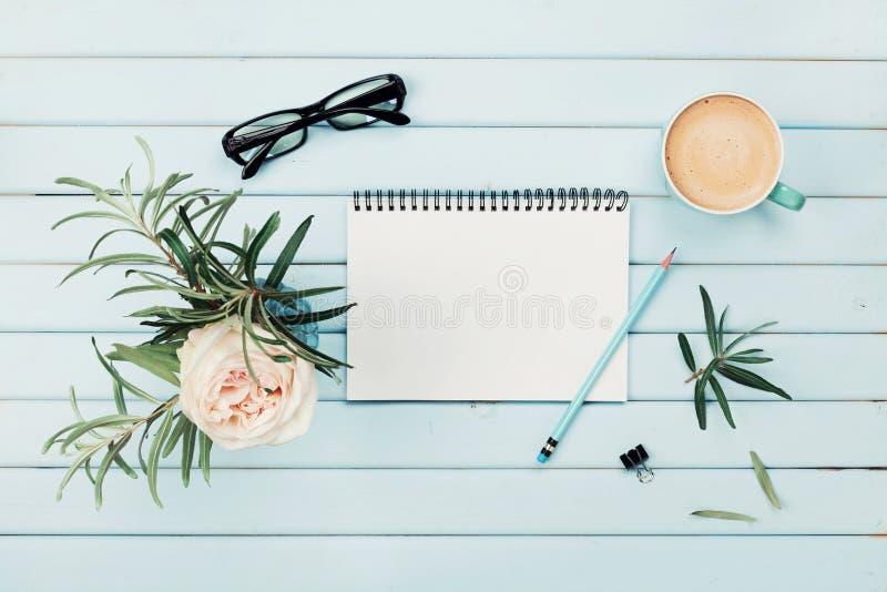 早晨咖啡杯、干净的笔记本、铅笔、镜片和葡萄酒玫瑰色花在花瓶在蓝色土气书桌顶上的视图 库存照片