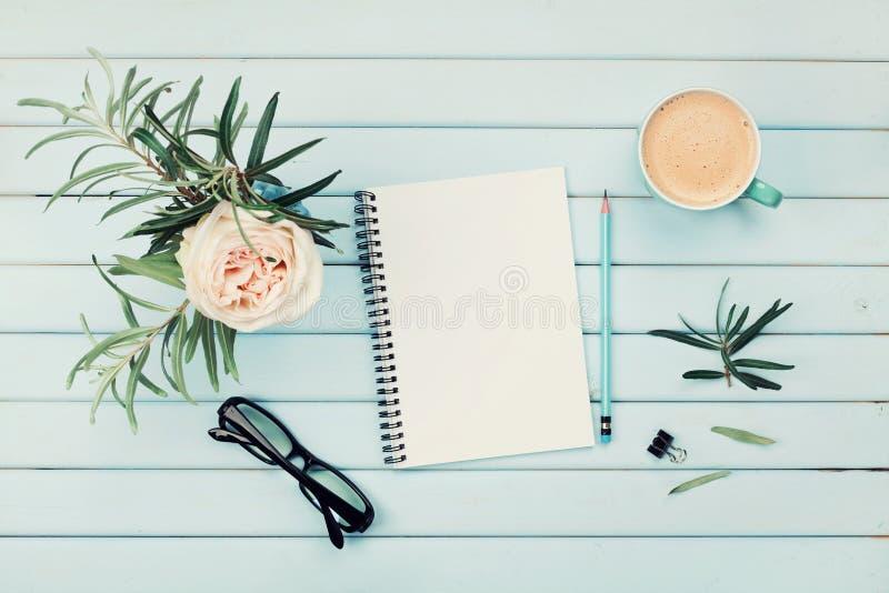 早晨咖啡杯、干净的笔记本、铅笔、镜片和葡萄酒玫瑰色花在花瓶在蓝色土气台式视图 平的位置 免版税库存图片