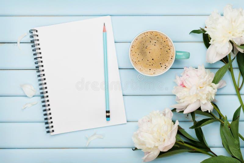 早晨咖啡杯、空的笔记本、铅笔和白色牡丹在蓝色木桌,舒适夏天早餐,顶视图,平展位置上开花 免版税库存图片