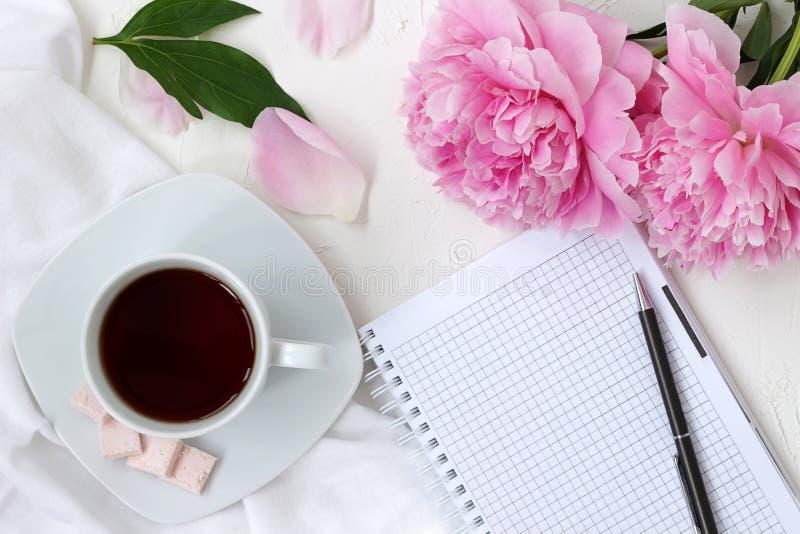 早晨咖啡杯和笔记薄在明亮的颜色与桃红色花 免版税库存图片