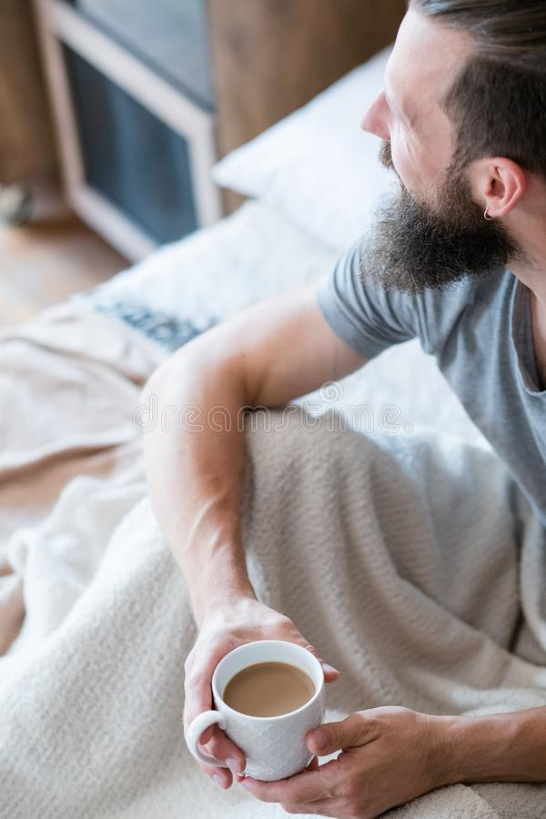 早晨咖啡温暖人习性床杯子 库存图片