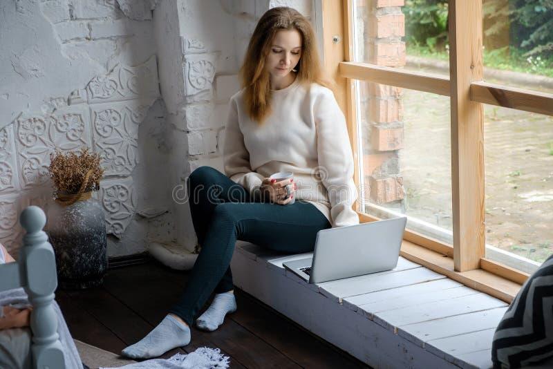 早晨坐与膝上型计算机书和饮料咖啡的窗台一美丽的少女的画象 库存图片