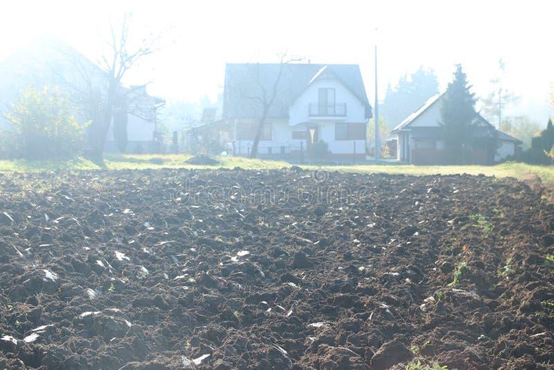 早晨太阳的光芒的新近地被犁的土地高昂在冷空气 春天在农村的野外工作 准备  免版税图库摄影