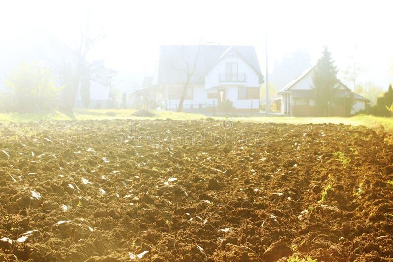 早晨太阳的光芒的新近地被犁的土地高昂在冷空气 春天在农村的野外工作 准备  库存照片