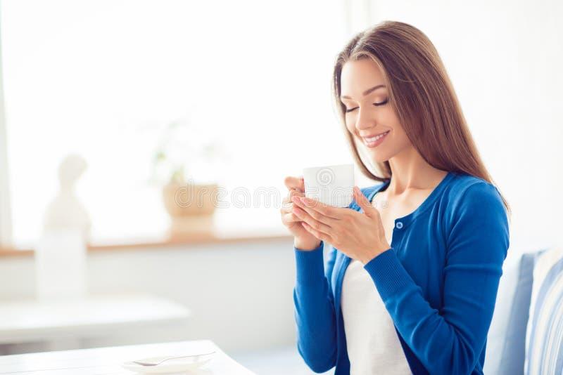 早晨好!关闭迷人的梦想的深色的女孩饮用的咖啡画象  她是困和轻松,在偶然蓝色 免版税库存图片