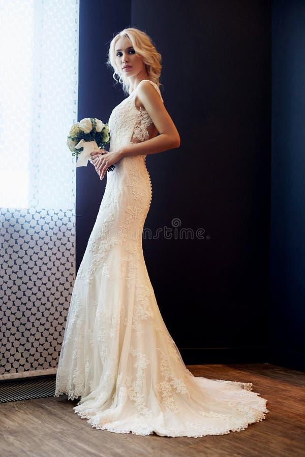 早晨新娘 一白色婚纱的一名妇女在她的手上的拿着一花束 准备好美丽的白肤金发的女孩为 免版税库存图片
