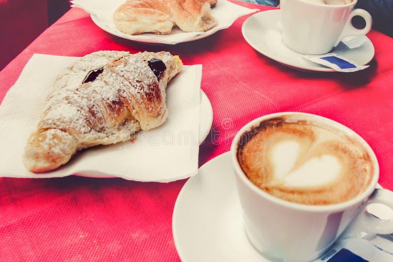 早晨早餐在意大利餐馆-新月形面包和一杯咖啡与心形的泡沫的 库存图片
