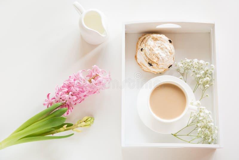 早晨早餐在有一个杯子的春天无奶咖啡用牛奶和酥皮点心在淡色,新鲜的桃红色hyacin花束  免版税库存图片