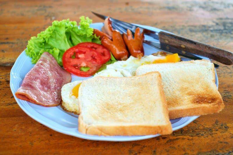早晨早餐用香肠、烟肉、鸡蛋和多士在木桌上 免版税库存图片
