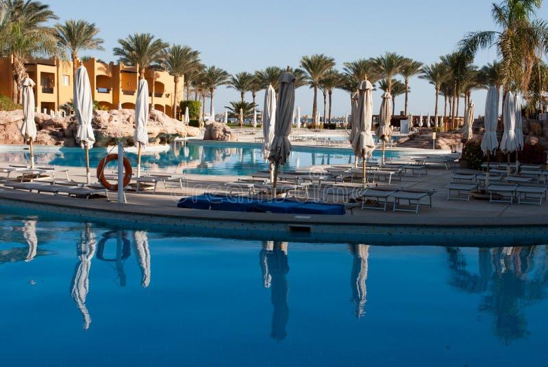 早晨水池边在旅馆里 人民不临近游泳池 闭合的水池伞 水池反射在镇静水中 在海运的掌上型计算机 免版税库存图片