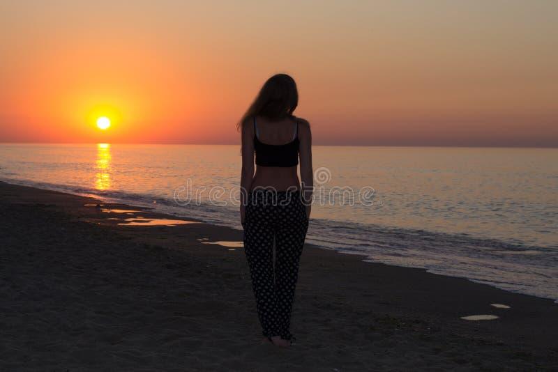 早晨海滩的女孩 免版税库存图片