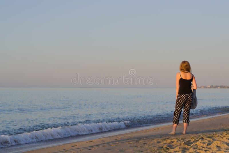 早晨海滩的女孩 免版税库存照片
