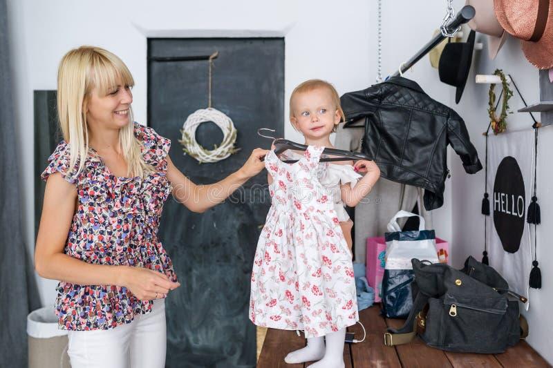 早晨照顾在家打扮她的女儿 小女孩选择礼服 图库摄影