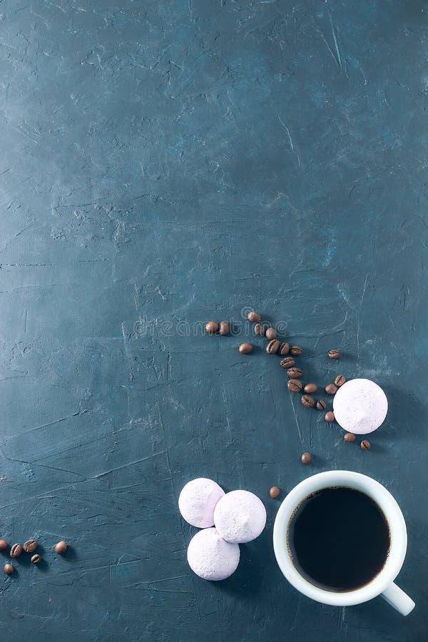 早晨芳香咖啡用被烘烤的蛋白甜饼,在黑混凝土 在视图之上 复制空间 分散的咖啡豆 空间为 库存照片