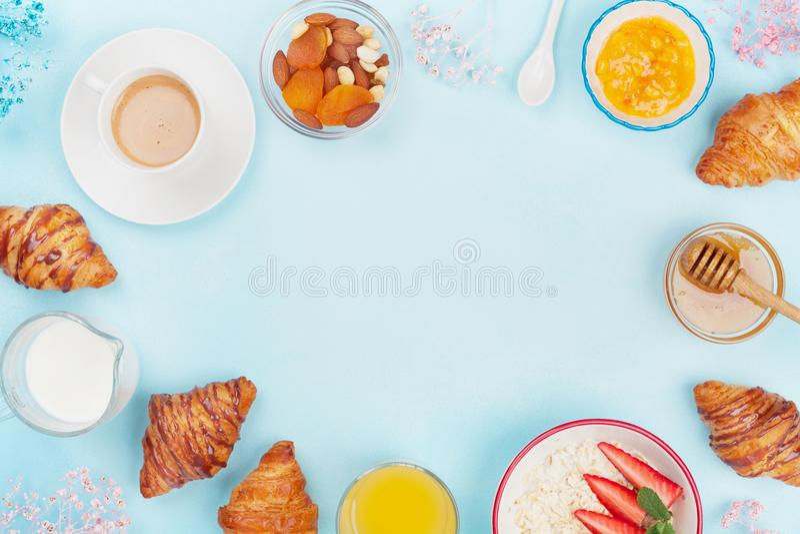 早晨轻快早餐用咖啡、新月形面包、燕麦粥、果酱、蜂蜜和汁液在蓝色台式视图 平的位置 免版税库存照片