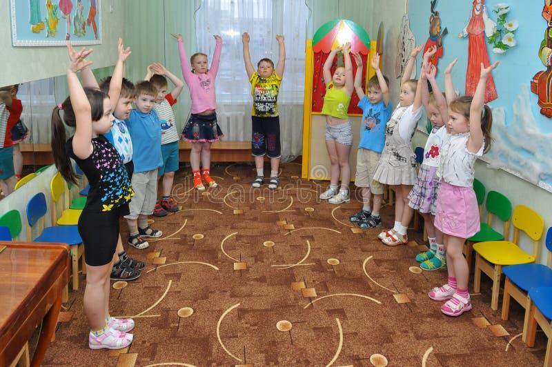 早晨锻炼对于一个小小组的儿童幼儿园 免版税库存照片