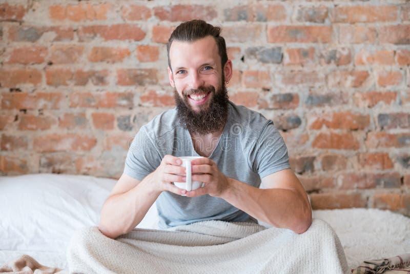 早晨饮料温暖微笑的行家床杯子 库存照片