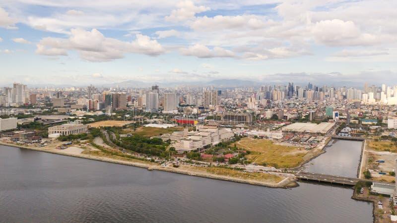 早晨,马尼拉市,从上方看 大港口城市全景 具有现代建筑和摩天大楼的城市 免版税库存图片