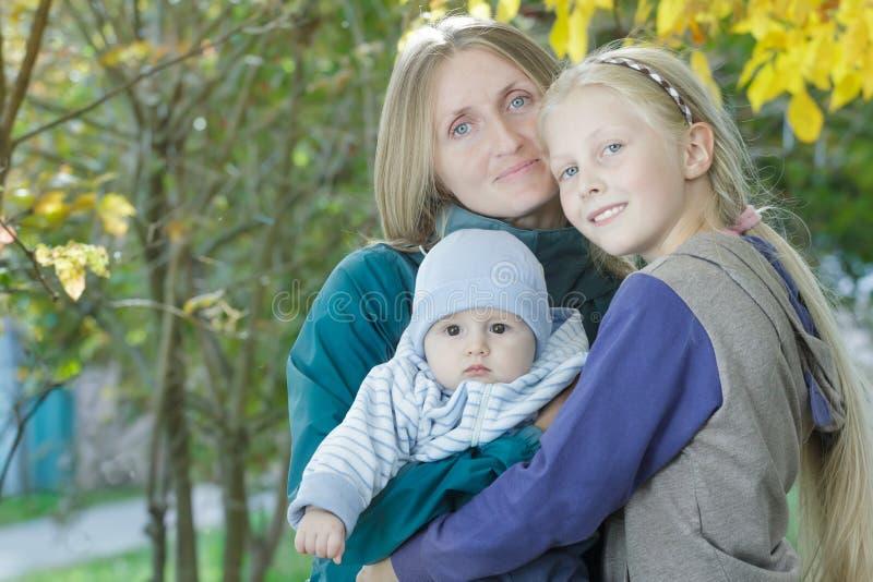 早期的快乐的母亲秋天室外家庭画象有两兄弟姐妹的黄色秋天灌木的离开背景 免版税库存图片