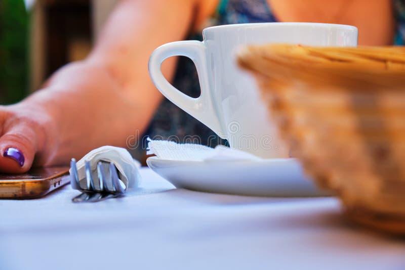 早餐、午餐或者晚餐概念与一杯白色咖啡、叉子和面包篮子,所有设定在妇女前面 免版税库存图片
