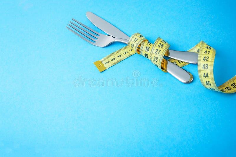 早餐、午餐或者晚餐的饮食食谱盘 叉子和刀子在蓝色背景的黄色测量的磁带被包裹 库存照片