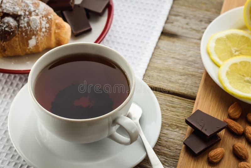 早餐、茶和新月形面包在桌上,柠檬,杏仁 库存照片