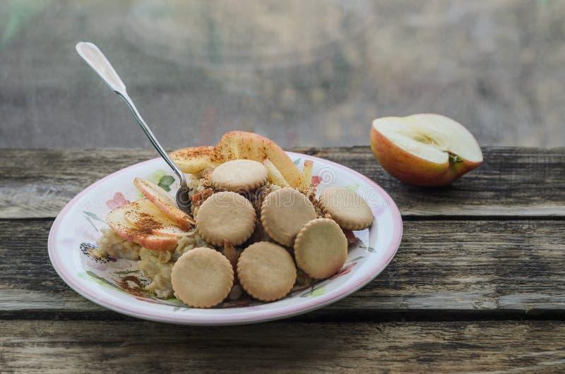 早餐与苹果和桂香五颜六色的盘,饼干的燕麦粥粥 库存图片