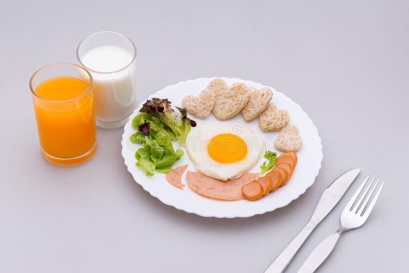 早餐包括荷包蛋,火腿,香肠,牛奶,桔子,全麦面包被塑造象心脏,新鲜蔬菜,投入了板材 免版税库存图片