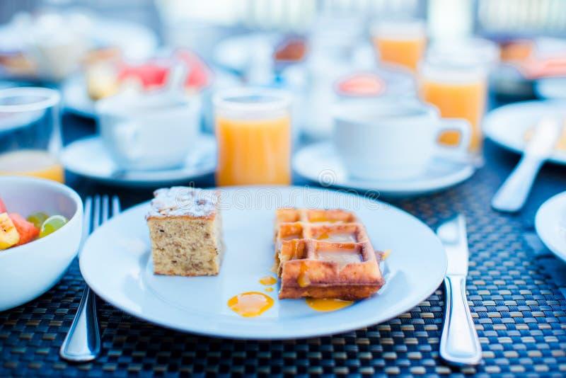 早餐和汁供食的新鲜水果沙拉、奶蛋烘饼、蛋糕、咖啡在手段餐馆 库存图片