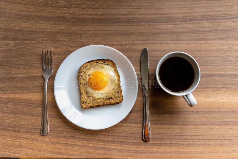 早餐咖啡概念煎的杯子鸡蛋 有被烘烤的面包和蛋和加奶咖啡杯子的白色板材 木纹理背景 免版税库存图片