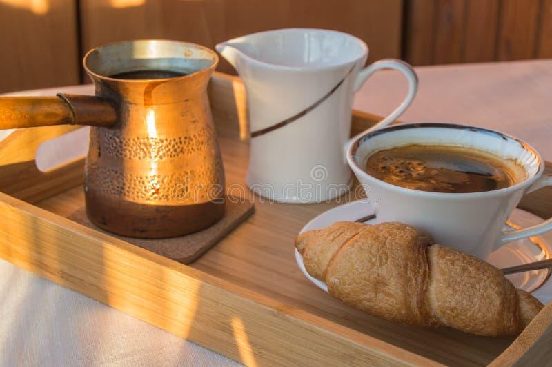 早餐在有铜罐、一杯咖啡和新月形面包的一个木盘子供应 在开放阳台的阳光早晨 库存照片