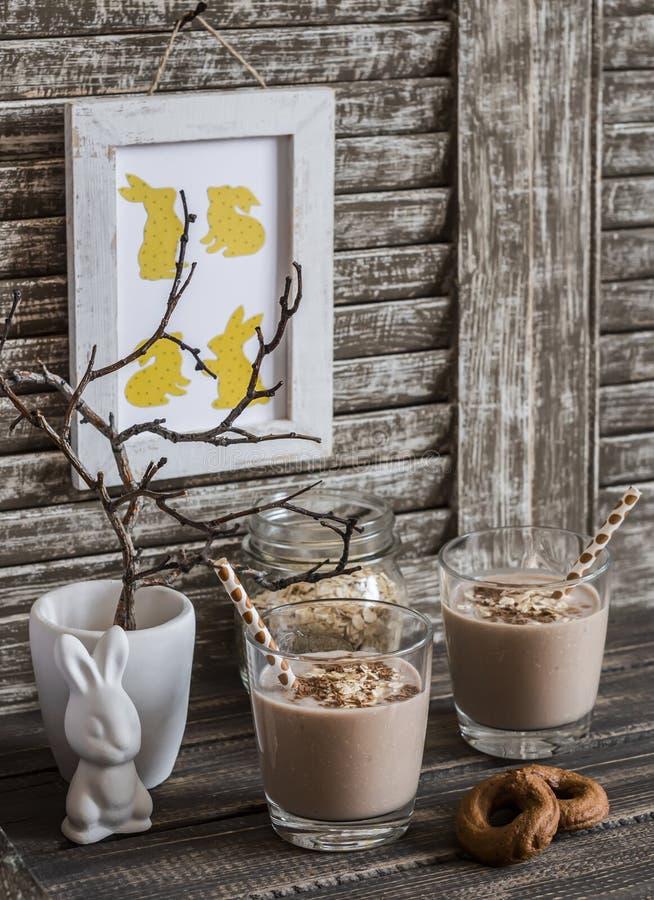 早餐巧克力、香蕉、燕麦粥圆滑的人和复活节装饰-复活节陶瓷兔子,在一个陶瓷花瓶的干燥分支和 图库摄影