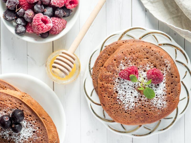 早餐巧克力薄煎饼用莓果、一杯咖啡与奶油的,蜂蜜和谷物 顶视图 免版税库存图片