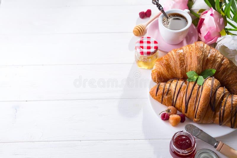 早餐新近地被烘烤的新月形面包装饰用果酱和巧克力,在木桌上的花在有拷贝空间的一个厨房里 免版税库存图片