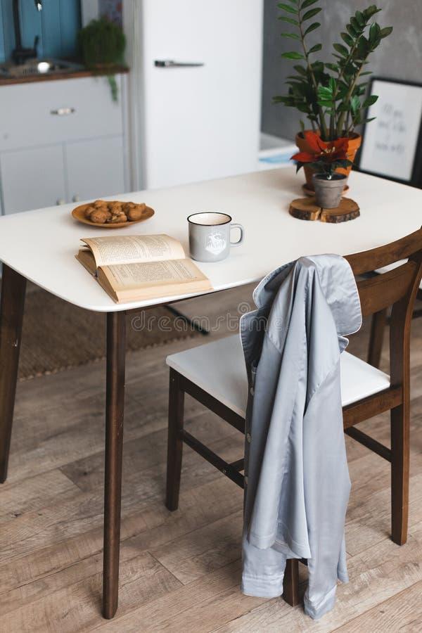 早餐时间和厨房地方有咖啡杯的在木书桌上有被打开的书的 库存照片