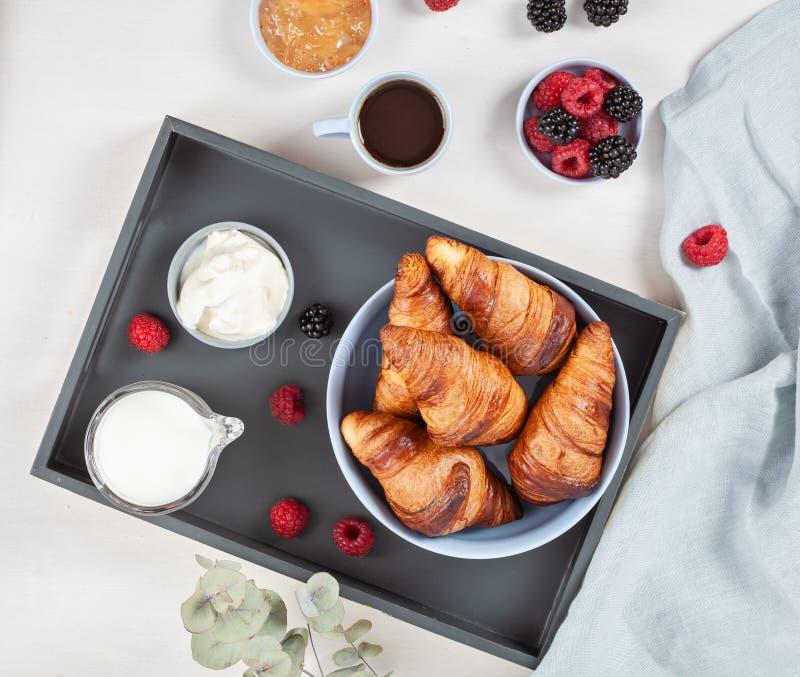 早餐服务用咖啡,新月形面包,新鲜的莓果,牛奶, c 免版税库存照片