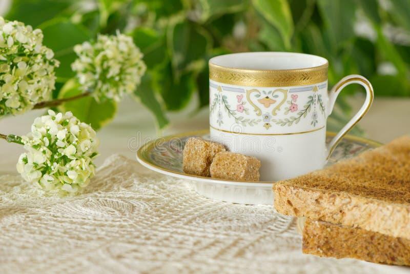 早餐桌在有一朵浪漫杯子、多士面包和花的庭院里 免版税库存照片