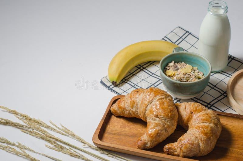 早餐桌用美味的新月形面包和谷物和香蕉和新鲜的牛奶 库存图片