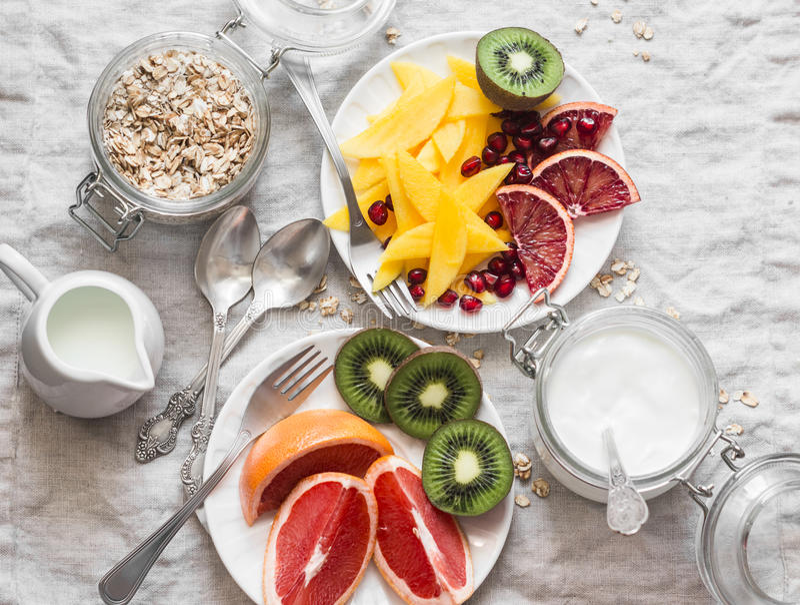 早餐桌 果子品种-芒果、猕猴桃,葡萄柚,橙色和希腊酸奶,燕麦在轻的背景,顶视图剥落 库存图片