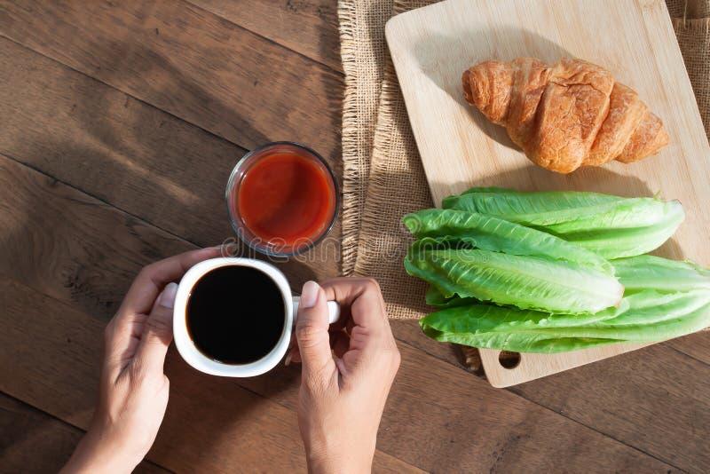 早餐概念创造性的平的位置  拿着咖啡杯用西红柿汁、新月形面包和菜的妇女手在桌上 免版税库存照片
