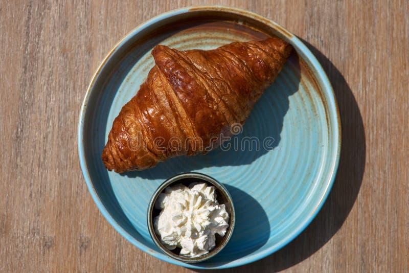 早餐概念 早晨,健康早餐新近地烘烤了与奶油奶酪的新月形面包在桌上的一块蓝色板材 免版税图库摄影