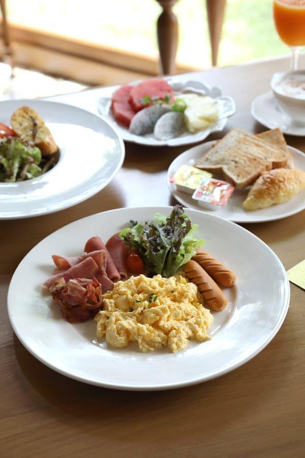 早餐炒蛋用烟肉香肠和沙拉在木背景 免版税库存照片