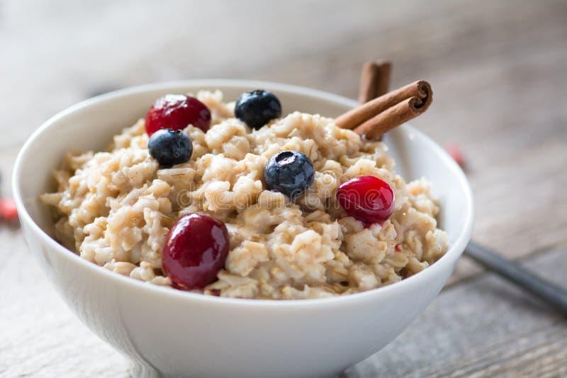 早餐燕麦粥粥用桂香、蔓越桔和蓝莓 库存照片